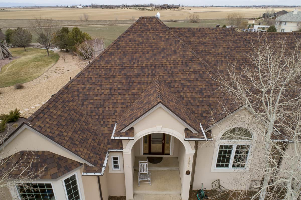 Tope view of a tan house with brown asphalt shingle roofing