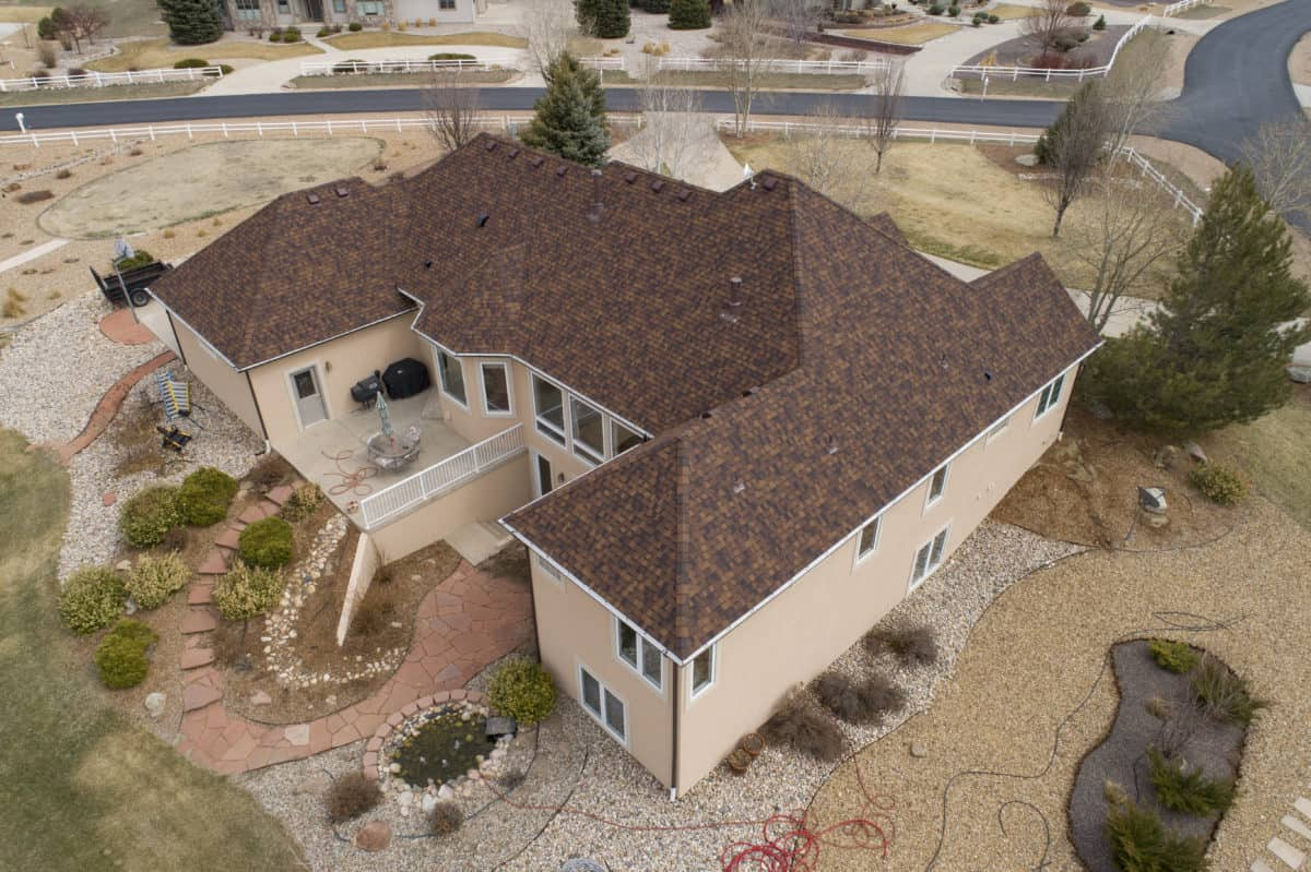 Aerial view of a tan house with burnt sienna Certainteed Landmark roof shingles